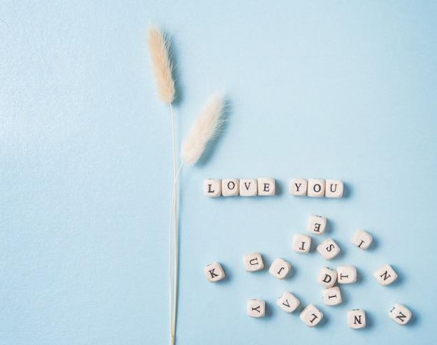 Minimalistische flache lage mit weißen getrockneten blumen und streuwürfeln mit dem wort liebe dich auf blauem hintergrund. konzept des valentinstags, des muttertags, des hochzeitstags. draufsicht und kopierraum