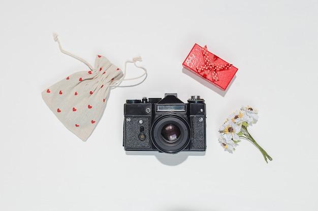 Minimalistische flache laienkomposition mit retro-kamera, roter geschenkbox, leinentasche mit roten herzformen und frühlingsfeldblume auf weißem hintergrund. trendy flat lay mockup für blogger, designer, fotografen