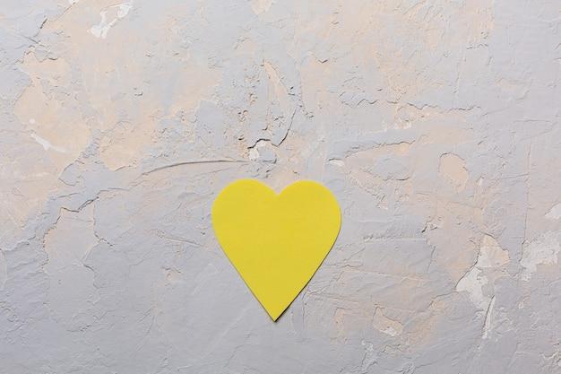 Minimalistische grußkarte des heiligen valentinstag in den grauen und gelben farben pantone 2021, papierherz auf strukturiertem hintergrund, flache lage