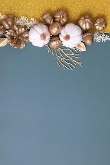 Minimalistische herbstwohnung mit kopienraum und goldenen eicheln, zapfen, blättern und kürbissen auf buntem hintergrund mit kopienraum-vertikalformat