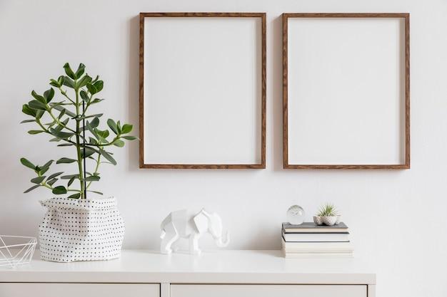 Minimalistische inneneinrichtung mit zwei braunen holzbilderrahmen auf dem weißen regal mit büchern, schöner pflanze in stilvollem topf und wohnaccessoires. weiße wand.