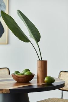 Minimalistische komposition auf dem design-holztisch mit früchten, tropischem blatt in vase, abstrakten gemälden und stilvollem stuhl