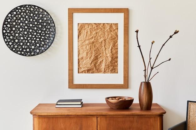 Minimalistische komposition des wohnzimmers mit braunem mock-up-bilderrahmen, pflanze, retro-sessel, getrocknetem tropischem blatt, dekoration und eleganten persönlichen accessoires in stilvoller wohnkultur. vorlage.