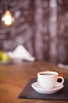 Minimalistische komposition einer tasse kaffee auf einer schwarzen steinplatte mit unscharfem hintergrund. leckerer kaffee. vintage-kneipe.