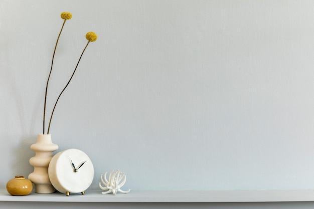 Minimalistische komposition im regal mit getrockneter blume in designvase, weißer uhr und accessoires. graue wand. platz kopieren.