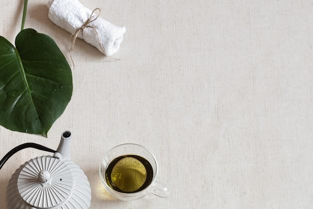 Minimalistische komposition mit grünem tee in einer tasse, einer teekanne und badezubehör. gesundheits- und schönheitskonzept.