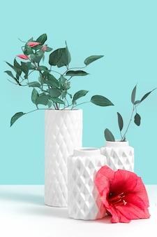 Minimalistische komposition mit zierpflanzen in weißer moderner keramikvase und roter blume auf grauem tisch gegen blauen hintergrund mit kopienraum für text. stillleben-modellkonzept für blumenladen
