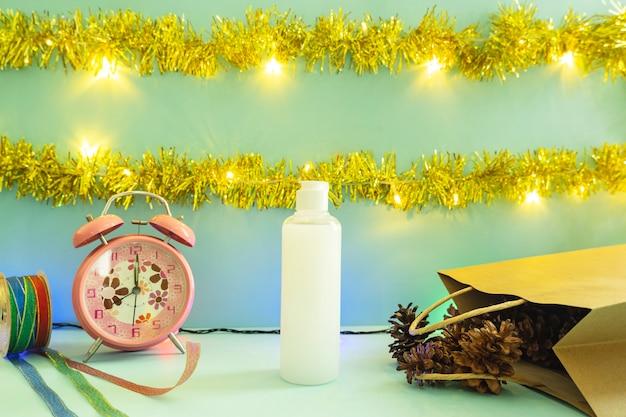 Minimalistische konzeptidee, die produkte anzeigt. kosmetische flaschen auf weihnachten und neujahrshintergrund. wecker. kiefernblume