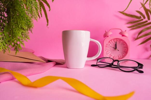 Minimalistische konzeptidee weiße kaffeetasse auf rosa hintergrund mit weckerdekoration, blättern und gläsern