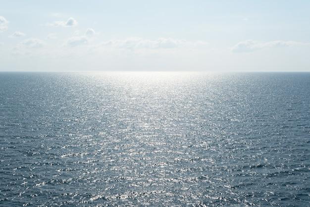 Minimalistische meereslandschaft mit sonnenreflexion auf wellen und blick auf die skyline mit kopienraum für text