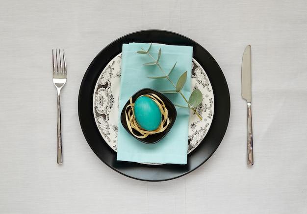 Minimalistische, moderne ostertabelleneinstellung mit schwarzem teller, türkisfarbenem ei, eukalyptuszweig.