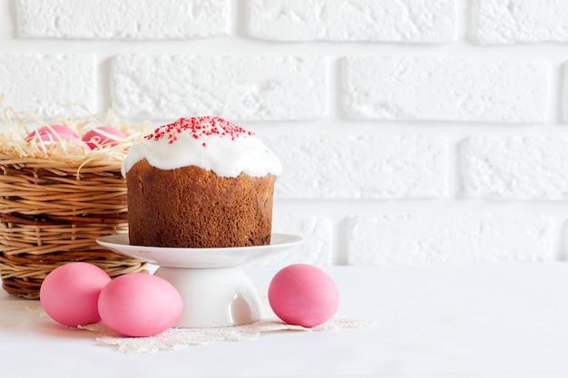 Minimalistische osterkomposition mit weidenkorb mit rosa gefärbten eiern und osterkuchen auf weißer oberfläche
