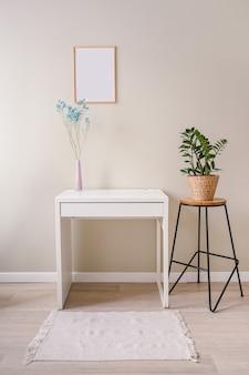 Minimalistische pastellfarben des weiblichen stilllebenarbeitsplatzes. weißer tisch, leerer poster-mock-up-rahmen, stilvolle rosa pudervase mit blauen trockenen blumen
