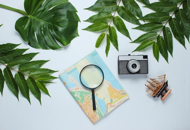 Minimalistische reise stillleben flach bellen stil. touristisches reisendes zubehör auf weißem hintergrund mit tropischem monsterblatt. draufsicht