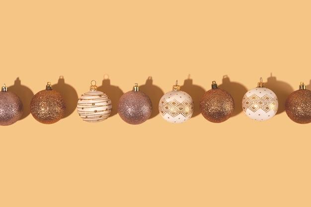 Minimalistische runde weihnachtskugeln in weiß und gold auf neutralem hintergrund