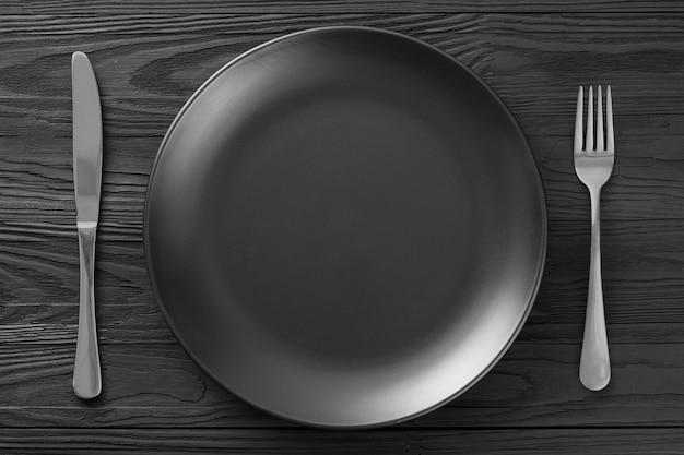 Minimalistische schwarze hintergrundtabelleneinstellung in einem restaurant. minimalismus der tabelleneinstellung