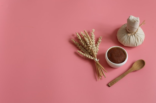 Minimalistische spa-komposition mit natürlichem peeling, kräutermassagebeutel, holzlöffel und weizen auf rosafarbenem hintergrund, kopierraum.