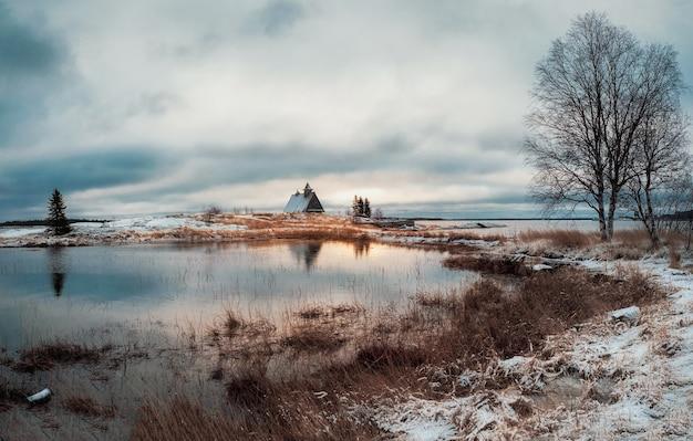 Minimalistische verschneite winterlandschaft mit authentischem haus am ufer im russischen dorf rabocheostrowsk.