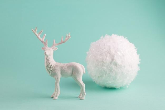Minimalistische winterkomposition mit white deer und großem dekorativem schneeball.