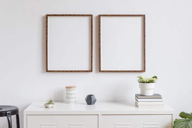 Minimalistische wohnkultur des interieurs mit zwei braunen holzfotorahmen auf dem weißen regal mit büchern, schöner pflanze in stilvollem topf und wohnaccessoires. weiße wand.