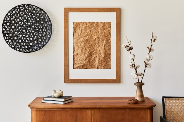 Minimalistische wohnzimmerkomposition mit braunem bilderrahmen, pflanze, retro-sessel, getrocknetem tropischem blatt, dekoration und eleganten persönlichen accessoires in stilvoller wohnkultur.