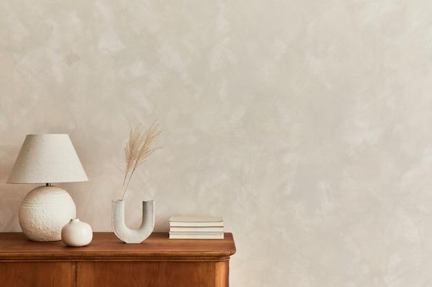 Minimalistische wohnzimmerkomposition mit holzkommode, tischlampe, trockenblume in vase, buch, dekoration und eleganten persönlichen accessoires in stilvoller wohnkultur. platz kopieren.