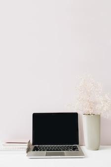 Minimalistischer arbeitsbereich des home-office-schreibtisches mit laptop, blumenstrauß auf rosa