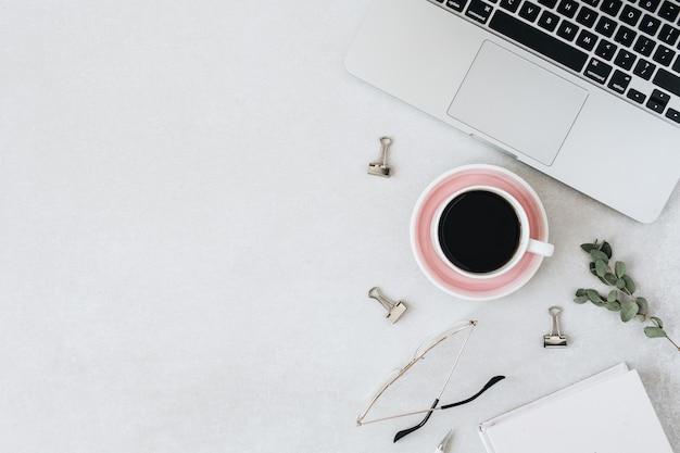 Minimalistischer arbeitsbereich für den home-office-schreibtisch. laptop, kaffee, gläser, notizbuch, eukalyptus auf leer