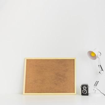 Minimalistischer arbeitsplatz mit korkboard und alter kamera