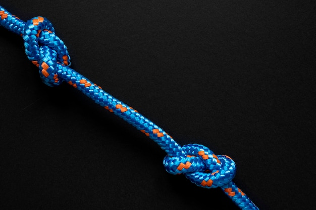Minimalistischer blauer seemannseilknoten auf schwarzem hintergrund