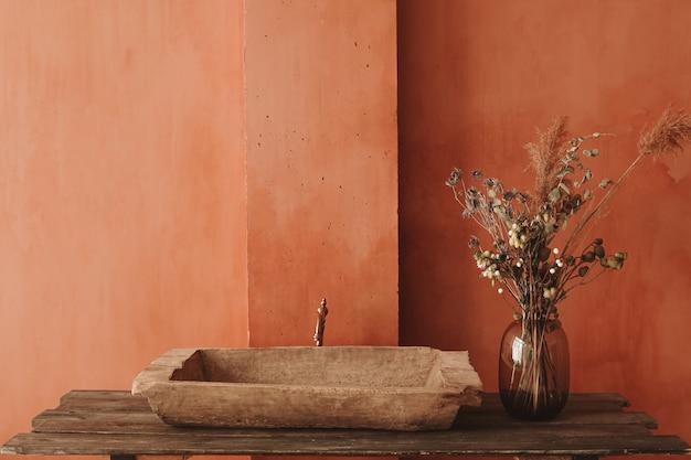 Minimalistischer einrichtungsstil. trockene blumen in einer glasvase, die auf einem hölzernen regal mit einem weinlesespülbecken am orangefarbenen wandhintergrund steht