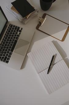 Minimalistischer home-office-schreibtisch-arbeitsplatz. laptop auf tisch mit kaffeetasse, papierblatt, briefpapier gegen weiße wand