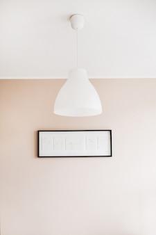 Minimalistischer innenraum des wohnzimmers mit weißer lampe, pastellrosa wand und malerei