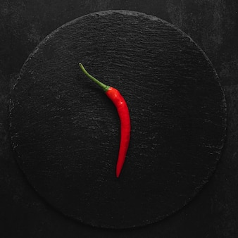 Minimalistischer roter heißer chilipfeffer auf dunklem hintergrund