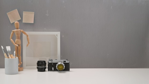 Minimalistischer schreibtisch mit weinlesekamera, material und kopienraum