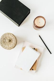 Minimalistischer schreibtischarbeitsplatz mit notizbuch auf weiß.