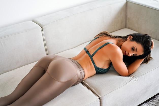 Minimalistisches bild der sinnlichen hübschen sportlichen frau, die auf beigem sofa, perfekt gebräuntem körper aufwirft, beige leggings und sport-bh tragend.