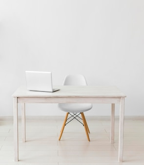 Minimalistisches büro mit tisch und laptop