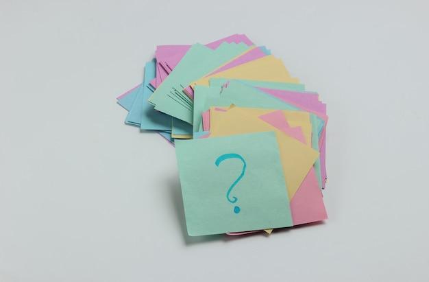 Minimalistisches bürokonzept viele memopapiere mit fragezeichen auf weißem hintergrund