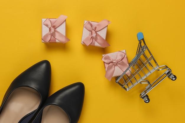 Minimalistisches einkaufskonzept. damen high heel schuhe, einkaufswagen, geschenkboxen mit schleifen auf gelbem hintergrund. geburtstag, muttertag, frauentagsgeschenke. draufsicht