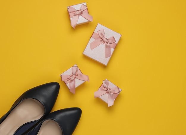 Minimalistisches einkaufskonzept. damen high heel schuhe, geschenkboxen mit schleifen auf gelbem hintergrund. geburtstag, muttertag, frauentagsgeschenke. draufsicht