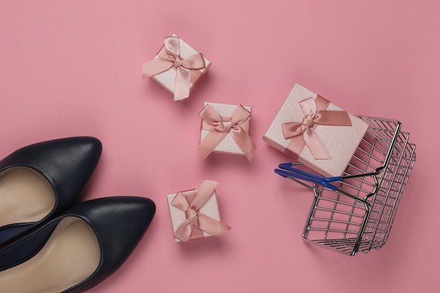 Minimalistisches einkaufskonzept. schuhe mit hohen absätzen für frauen, einkaufskorb, geschenkboxen mit schleifen auf einem rosa pastellhintergrund. geburtstag, muttertag, frauentagsgeschenke. draufsicht