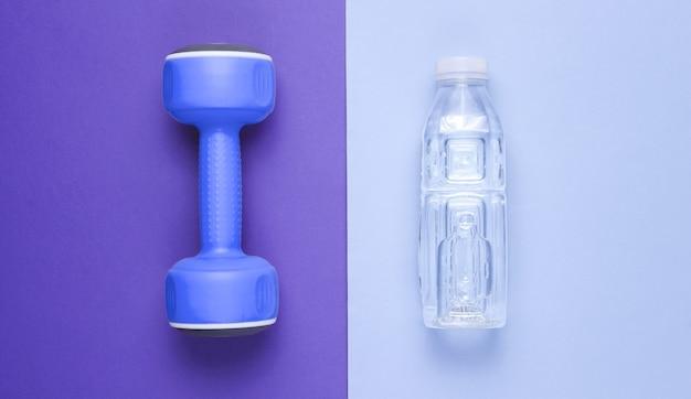 Minimalistisches fitnesskonzept. hantel, flasche wasser auf farbig