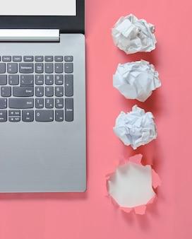 Minimalistisches geschäftskonzept. notizbuch, zerknitterte papierkugeln, auf rosa mit einem zerrissenen loch