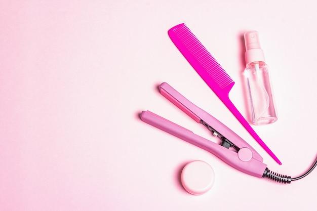Minimalistisches haarpflegekonzept mit haarglätter, pinsel, spray und öl
