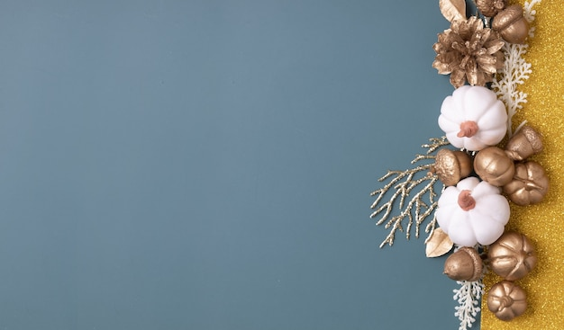 Minimalistisches herbstbanner mit kopienraum und goldenen eicheln, zapfen, blättern und kürbissen auf buntem hintergrund.