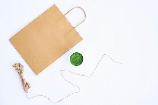 Minimalistisches herbstkonzept. papiertüte, blumentopf, sackleinengarn isoliert auf weißem papierhintergrund