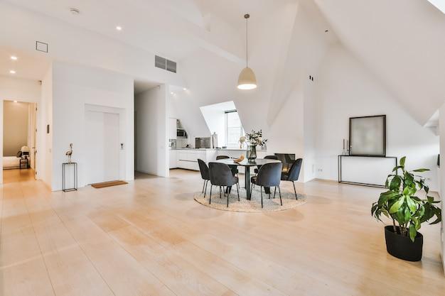 Minimalistisches innendesign einer geräumigen dachgeschoss-loft-wohnung mit weißen wänden und parkettboden, die mit einem runden tisch und stühlen ausgestattet ist