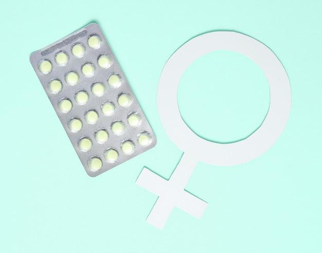 Minimalistisches konzept der frauenmedizin. pillen, weibliches geschlechtssymbol auf blauem hintergrund.