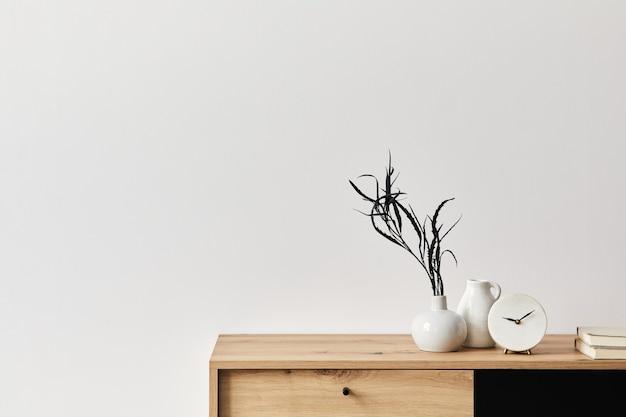 Minimalistisches konzept der wohnzimmereinrichtung in eleganter wohnung mit holzkommode, blatt in keramikvase, uhr und eleganten persönlichen accessoires in moderner wohnkultur. platz kopieren.. .